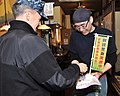 U.S. Navy Capt. Chris Rodeman, left, the commanding officer of Naval Air Facility Misawa, gives the owner of Antaga Taisho Restaurant a friendship coin while on a joint downtown patrol of Misawa, Japan, Dec. 17 131217-N-DP652-050.jpg
