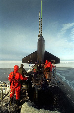 USS Pogy (SSN-647) - Having surfaced in the Arctic ice pack, crew members from the Pogy assemble a topside deck enclosure to provide protection from the elements while water samples are collected and cataloged in 1996.