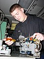 US Navy 030211-N-9403F-001 Aviation Electronics Technician Airman Daniel Cohick, from Newport, Pa., performs maintenance on a wave guide assembly in preparation for operational testing.jpg