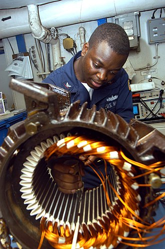 Electrician - US Navy electrician's mate rewiring the stator of an induction motor.