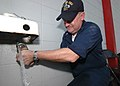 US Navy 050914-N-8933S-003 Aviation Structural Mechanic 1st Class Roger Clites prepares a connection for one of two homemade sinks. Sailors assigned to the amphibious assault ship USS Iwo Jima (LHD 7).jpg