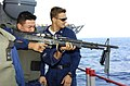 US Navy 051017-N-4207M-001 Gunner's Mate 3rd Class Ross Melone, right, observes Religious Program Specialist 3rd Class Sergio Rivassorto, as he fires an M-60 machine gun.jpg