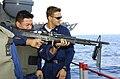 US Navy 051017-N-4207M-001 Gunner's Mate 3rd Class Ross Melone, right, observes Religious Program Specialist 3rd Class Sergio Rivassorto, as he fires an M-60 machine gun.jpg