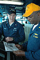 US Navy 070403-N-7128A-002 Aerographer's Mate 2nd Class Ryan Sorge, left, updates Office of the Deck, Lt. Cmdr. Joseph Baxter, on current weather conditions for flight operations aboard the nuclear-powered aircraft carrier USS.jpg