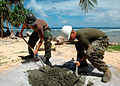 US Navy 070829-N-9421C-084 Construction Mechanic Constructionman Apprentice Matthew Blair and Hospitalman Cody Reedy, from Naval Mobile Construction Battalion (NMCB) 7, mix cement for a fence post during an engineering civic ac.jpg