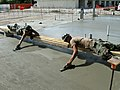 US Navy 081107-N-2788L-006 Builder 2nd Class LeeAnn Schott and Builder 2nd Class Anthony Morman take out the lines from the bullfloat for a level surface.jpg