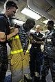 US Navy 090611-N-5242D-221 Damage Controlman 1st Class James Harry, Damage Controlman Fireman Jason King and Djiboutian Navy Sublieutenant Moussa Hanfare help Djiboutian Navy Cpl. Abdoullauder Issa remove a fire-fighting ensemb.jpg