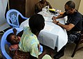 US Navy 100317-N-7948C-105 Cmdr. Antonio Rodriquez, from San Juan, Puerto Rico, performs a medical checkup on a Ghanaian woman and her child during a medical outreach program.jpg