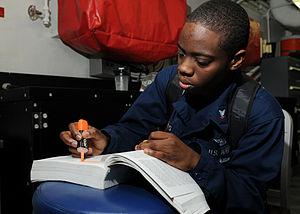 US Navy 120204-N-TU894-044 Aviation Ordnanceman 3rd Class Angela M. Roberts studies for an advancement exam aboard the aircraft carrier USS George.jpg