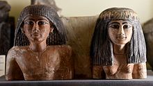 Upper part of a statuette of an Egyptian man and his wife. 18th Dynasty. From Egypt. From the Amelia Edwards Collection. Now housed in the Petrie Museum of Egyptian Archaeology, London.jpg
