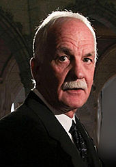A photograph of a man with white hair and a white moustache facing the right and looking just to the left of the viewer while wearing a necktie