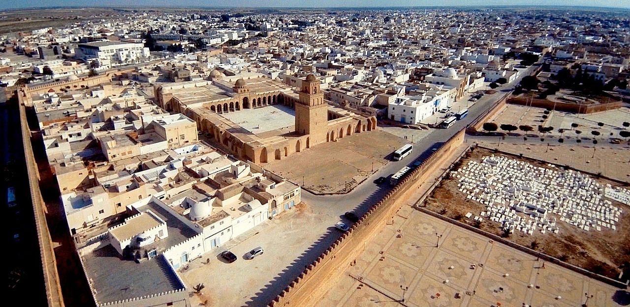 Photographie montrant une vue aérienne de la Grande Mosquée de Kairouan. Celle-ci est située à l'extrémité nord-est de la médina, à proximité des remparts dont elle n'est séparée que par une esplanade.