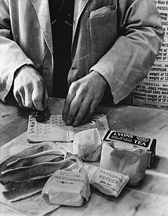 War effort - Civilian rationing: A shopkeeper cancels the coupons in a British housewife's ration book