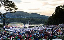 View of an amphitheater in front of a river with rolling hills in the background, with West Point cadets in front of the stage and performance attendees in the foreground