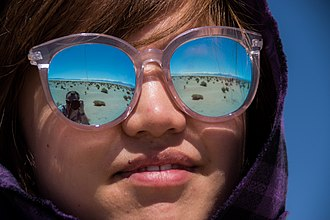 Optical coating - A woman wears sunglasses featuring a highly reflective optical coating