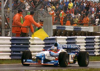 1997 British Grand Prix - Alexander Wurz passes a yellow flag during the race.