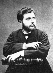 A young man, lightly bearded, sits in a posed position, facing half-right. He is formally dressed in dark clothes, and is holding a large book or scroll