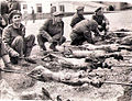 1958 - Greek soldiers roasting Easter lambs on open spits.jpg