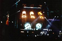 An elaborate concert stage at night. Three cars hang at the stage's rear shining lights towards the performance. Video screens are located behind and to the sides of the stage.