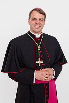 L évêque Stefan Oster portant la soutane avec un liseré et des boutons de  couleur cramoisie avec une calotte et une ceinture violettes et la croix  pectorale 2f0cc28832d