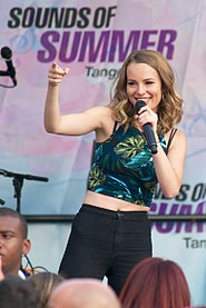 Young, blonde-haired woman gesturing towards her audience while smiling and singing into a hand-held microphone. She is outfitted in a floral-themed tank top and black pants; her midriff is exposed.