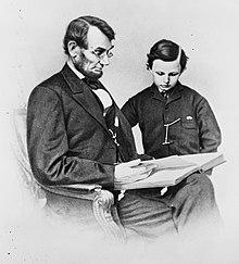 Photo en noir et blanc montrant un homme assis lisant, un jeune garçon à ses côtés.