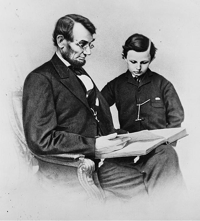 A seated Lincoln holding a book as his young son looks at it