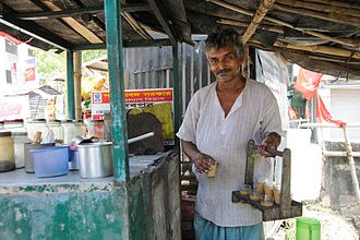 Masala chai - A man in Kolkata, India with a tray for serving nine glasses of chai