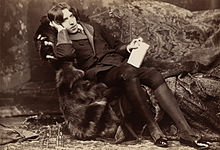 A tall man rests on a chaise longue, facing the camera. On his knees, which are held together, he holds a slim, richly bound book, he wears knee breeches which feature prominently in the photograph's foreground.