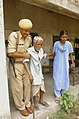 A senior citizen being helped by CRPF Jawan after casting his vote in 3rd phase of State Assembly Elections-2006 at Shyamnagar in North 24 Pargana, West Bengal on April 27, 2006.jpg