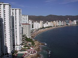 High view of the beachfront condos and hotels on the left, the long curved beach, Pacific ocean on the right