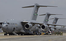 Vehicles and personnel unloading supplies from three gray C-17s parked together for victims of Hurricane Katrina.
