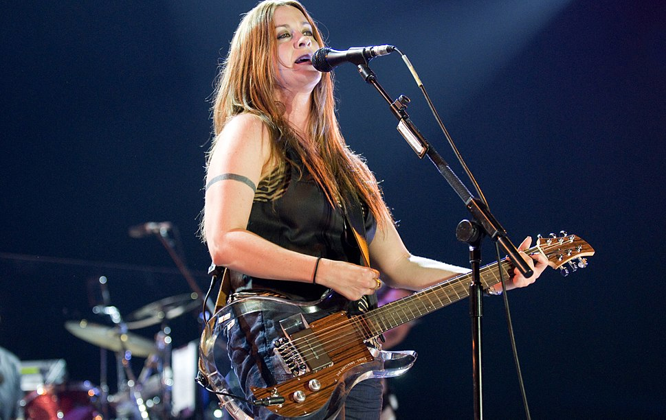 A woman in jeans and a black vest, holding a transparent guitar and standing behind a microphone stand. In the background is a drum set.
