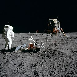 Astronaut Buzz Aldrin with scientific equipment, US flag, television camera and Apollo Lunar Module at Tranquility Base. Photo by Neil Armstrong