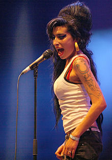 Winehouse singing in front of a microphone, looking to the side.