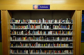 Audiobook - An audiobook collection in a library. A mix of cassette tape and CD-ROM formats.