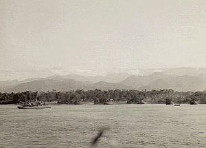 Salamaua–Lae campaign - 4 September 1943. The Australian 9th Division makes its amphibious landing east of Lae. LSTs can be seen completing their unloading. A tug is in the foreground and the Saruwaged Range is in the distance.
