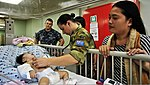 Australian Army Capt. Kerry McKinnell, top center, checks the vitals of a four-month-old Indonesian girl who had surgery to fix her cleft lip aboard Military Sealift Command hospital ship USNS Mercy (T-AH 19) 120602-O-ZZ999-009.jpg