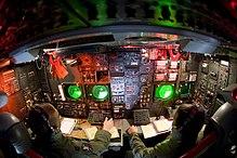 Cubierta inferior de un B-52, con instrumentos y pantallas predominantemente en la pared lateral del avión.  Esta estación está a cargo de dos miembros de la tripulación.