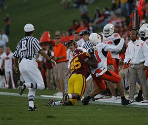Horse-collar tackle - Example of a horse-collar tackle made by an  UI player (red and gold). The tackler's right hand has grabbed the runner's collar and is using it to pull him down from behind.