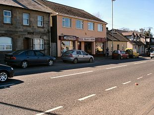 "The village centre, located on the <a href=""http://search.lycos.com/web/?_z=0&q=%22A2%20road%20%28Northern%20Ireland%29%22"">A2</a>"