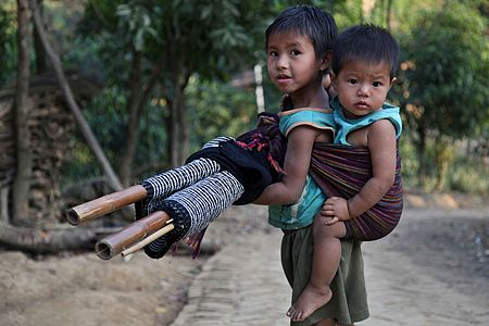 A tribal kid tied her little sister in her back. Farukpara, Bandarban, Bangladesh.