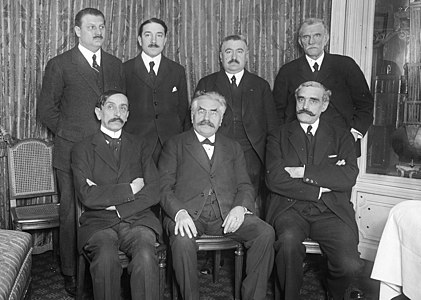 Zwart-witfoto van zeven mannen met snor in pakken (drie zittende, voorgrond en vier staande, achtergrond)