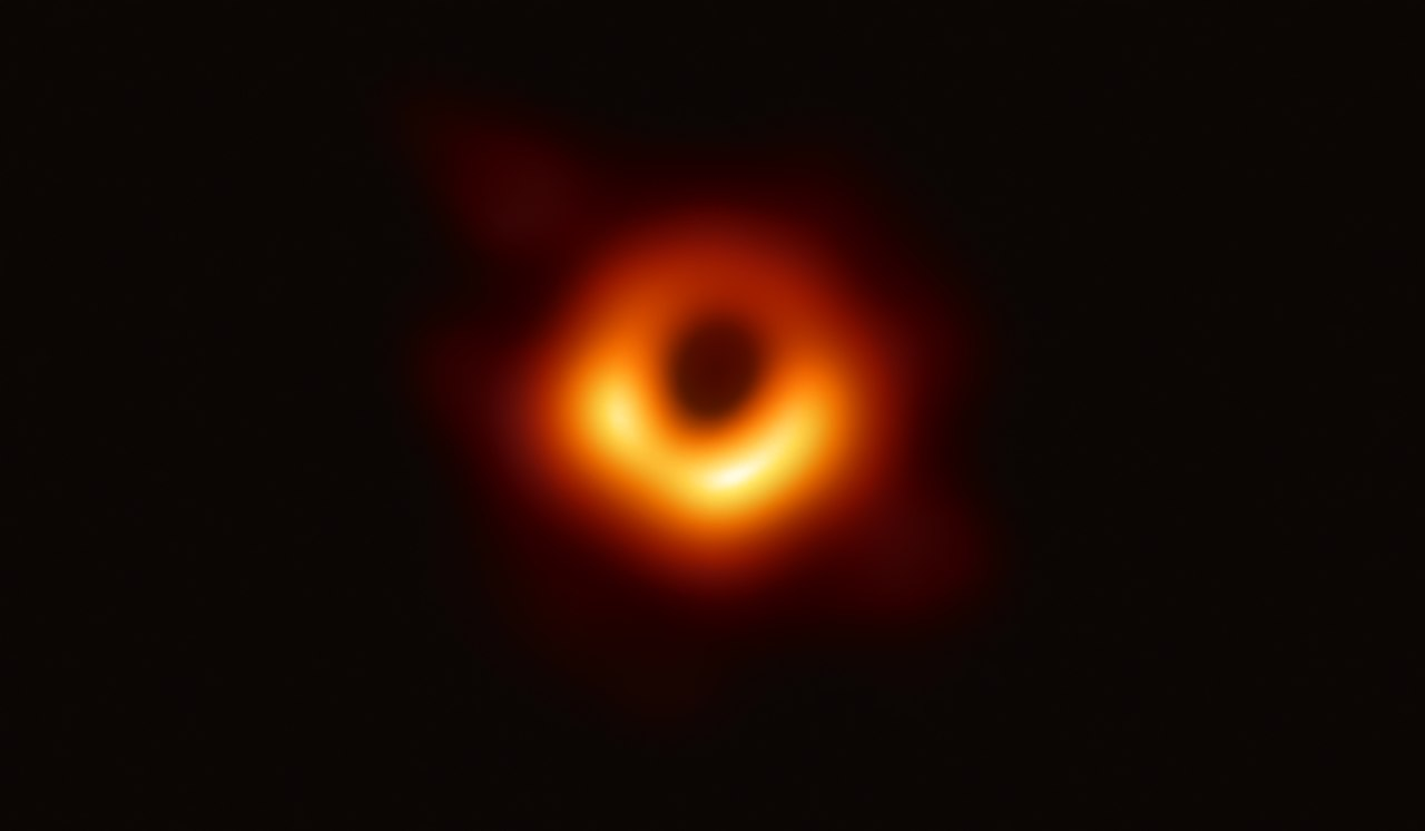 photograph of a black hole surrounded by orange light