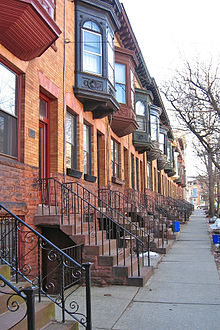 A view down a city sidewalk with identical orange brick rowhouses, all with a projecting upper window