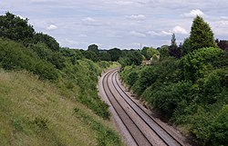 A double-tracked railway line passes through a cutting. The lines are clean and well-maintained, with fresh ballast. The banks of the cutting have light foliage, with few buildings visible nearby.