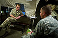 British Army Lt. Col. J.M. Senior, left, the commanding officer of the Light Dragoons, talks with U.S. Army Capt. Ryan Yaun, a trainer at the Joint Multinational Readiness Center, during a computer-simulated 140827-A-WB953-408.jpg