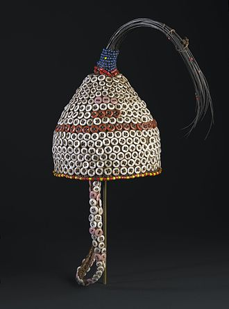 Initiation - This hat would only have been worn by initiates to Kindi, the highest level of Bwami. Tail hair of an elephant, a metaphor for Kindi, crowns the hat. European-made buttons began to replace cowrie shells as prestige items on such Bwami paraphernalia as the Western presence grew in eastern Congo in the early twentieth century