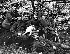 Une photo noir et blanc d'un groupe de sept hommes en tenue militaire de l'armée allemande de 1915. Deux hommes se tiennent debout, devant un mur de briques qui forme l'arrière-plan de la photo, et derrière quatre autres hommes assis dont Adolf Hitler, à droite, reconnaissable à son épaisse moustache. Au premier plan, un septième homme tout sourire se tient allongé sur le côté, dans l'herbe, aux pieds des quatre hommes assis.
