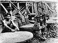 COLLECTIE TROPENMUSEUM Een man naast een driekoppige osa'osa een stenen zetel als eerbetoon aan dorpshoofden en voorouders TMnr 10004911.jpg